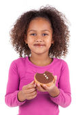 Little African Asian girl eating a chocolate cake — Stock Photo
