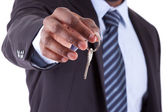 Young African American businessman holding a house key — Stockfoto