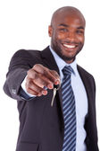 Young African American businessman holding a house key — Stock Photo