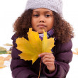 Little african asian girl wearing winter clothes playing with le — Stock Photo #17140465