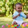 Little african american baby boy playing in the grass — Stock Photo #17865885