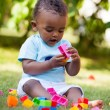 Little african american baby boy playing in the grass — Stock Photo #17866005
