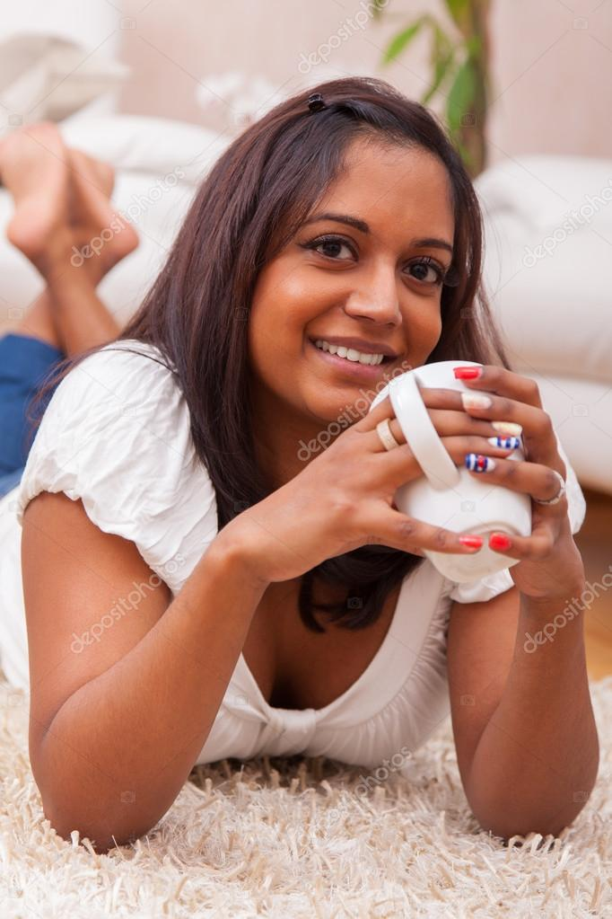 Young beautiful indian woman drinking coffee , lying on the floor while — Stock Photo #20017093