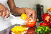 African American womans hand slicing a tomatoe — Stock Photo