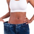 Young african woman in old jeans pant after losing weight — Stock Photo
