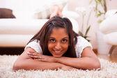 年轻快乐的印度女人躺在地板上 — 图库照片