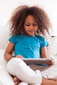 Little african asian girl using a tablet pc — Stock Photo