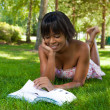 Outdoor portrait of young black woman reading a book — Stock Photo #23254802