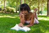 Outdoor portrait of young black woman reading a book — Stock Photo