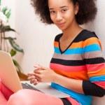 Постер, плакат: Black African American teenage girl with a afro haircut using a