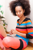 Black African American teenage girl with a afro haircut using a — Stockfoto