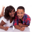 Happy young black African American couple lying down on the floo - Foto de Stock