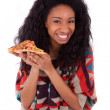 Young black african american teenage girl eating a slice of pizz — Stockfoto