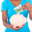Black african american woman inserting a euro bill inside a smil — Stock Photo