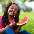 Outdoor portrait of a cute young black little girl eating waterm — Stock Photo #25087143