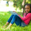Outdoor portrait of a cute young black little girl reading a boo — Stock Photo #25087199