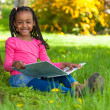 Outdoor portrait of a cute young black little girl reading a boo — Stock Photo #25087219