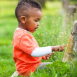 Outdoor portrait of a cute young little black boy playing outsi — Stock Photo