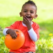 Outdoor portrait of a cute young little black boy playing with — Stock Photo
