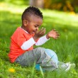 Outdoor portrait of a cute young little black boy playing with — Stock Photo #25087467