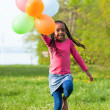 Outdoor portrait of a cute young little black girl playing with — Stock Photo