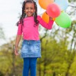 Outdoor portait of a cute young little black girl playing with — Stock Photo