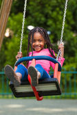 Outdoor portrait of a cute young black girl playing with a swin — Stock Photo