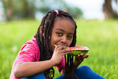 Outdoor portrait of a cute young black little girl eating waterm — Stock Photo