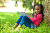Outdoor portrait of a cute young black little girl reading a boo — Stock Photo
