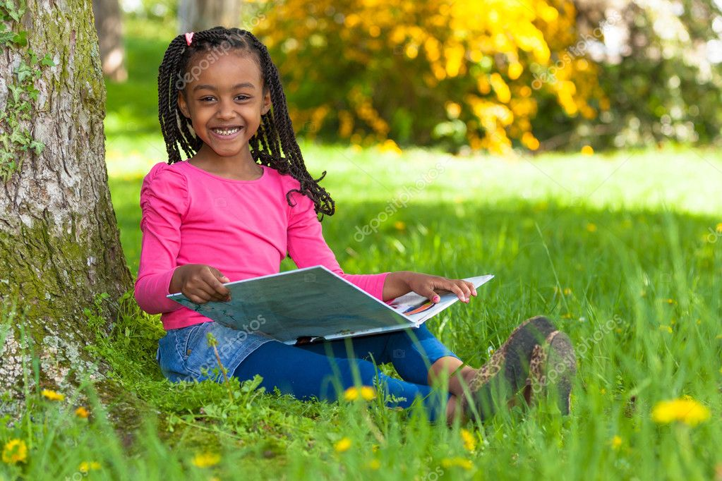 读一本书-非洲的可爱年轻黑人小女孩的室外肖像
