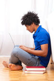 Young african american student using a laptop - African — Foto de Stock