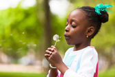 Outdoor portrait of a cute young black girl blowing a dandelion — Stock Photo