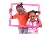 Little african american girls holding a picture frame — Stock Photo