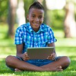Stock Photo: Outdoor portrait of student black boy using a tactile tablet - A