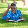 Outdoor portrait of student black boy reading a book - African p — Photo