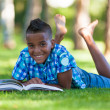 Outdoor portrait of student black boy reading a book - African p — Stock Photo