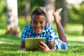 Outdoor portrait of student black boy using a tactile tablet - A — Stock Photo