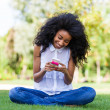 Stock Photo: Teenage black girl using a phone, lying on the grass - African p