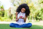 Preta adolescente usando um telefone, deitado na grama - Africano p — Fotografia Stock