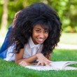 Stock Photo: Young student girl reading a book in the school park - African p