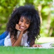 Young student girl reading a book in the school park - African p — Stock Photo #30239021