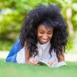Young student girl reading a book in the school park - African p — Stock Photo #30239037