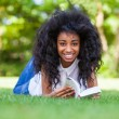 Young student girl reading a book in the school park - African p — Stock Photo