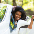 Young black teenage driver holding car keys driving her new car — Stock Photo