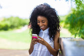 Outdoor portrait of a teenage black girl using a mobile phone - — ストック写真