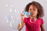 Little African Asian girl blowing soap bubbles  — Stock Photo