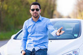 Young latin american driver holding car keys driving his new car — Stock Photo