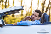 Young latin american driver making a phone call while driving — Stock Photo