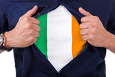 Young sport fan opening his shirt and showing the flag his count — Stock Photo