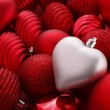 Silver christmas heart on red baubles — Stock Photo #5141277